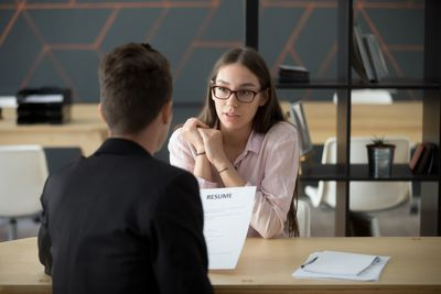 Confident millennial female applicant talking at job interview answering questions