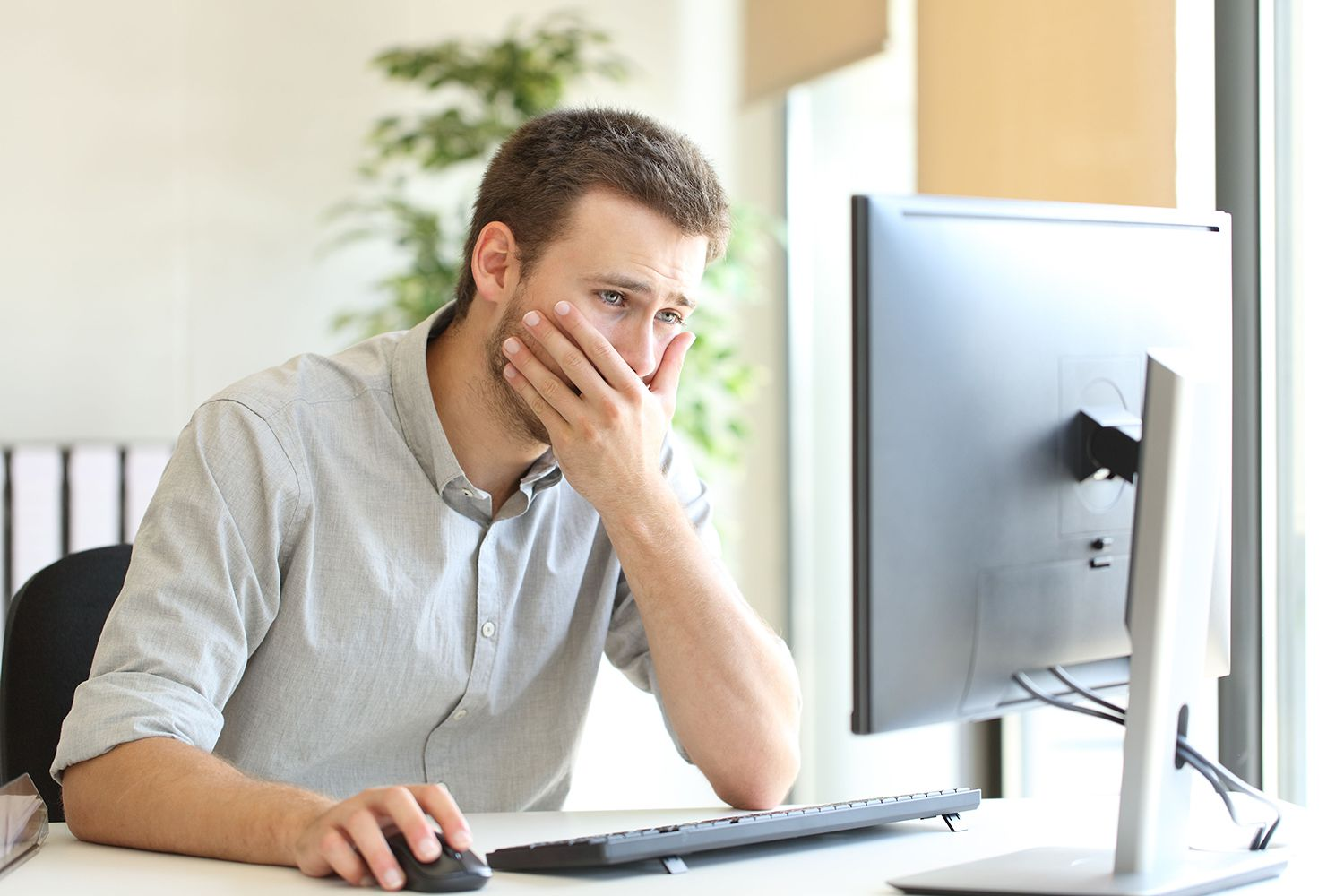 Man looking at computer with hand over mouth, worried about his mistake