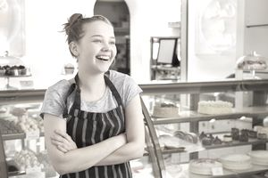 Girl working in bakery looking away smiling