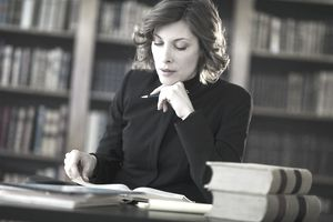 Legal Professional Studying in a Library With Books