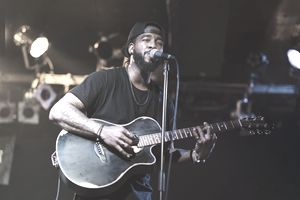 Black man playing acoustic guitar and singing on stage.