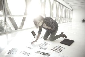 photographer kneeling on floor reviewing proofs in a brightly lit space
