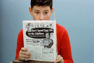 young boy reading magazine with an effective print ad on the back cover