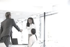 Business people shaking hands in office building