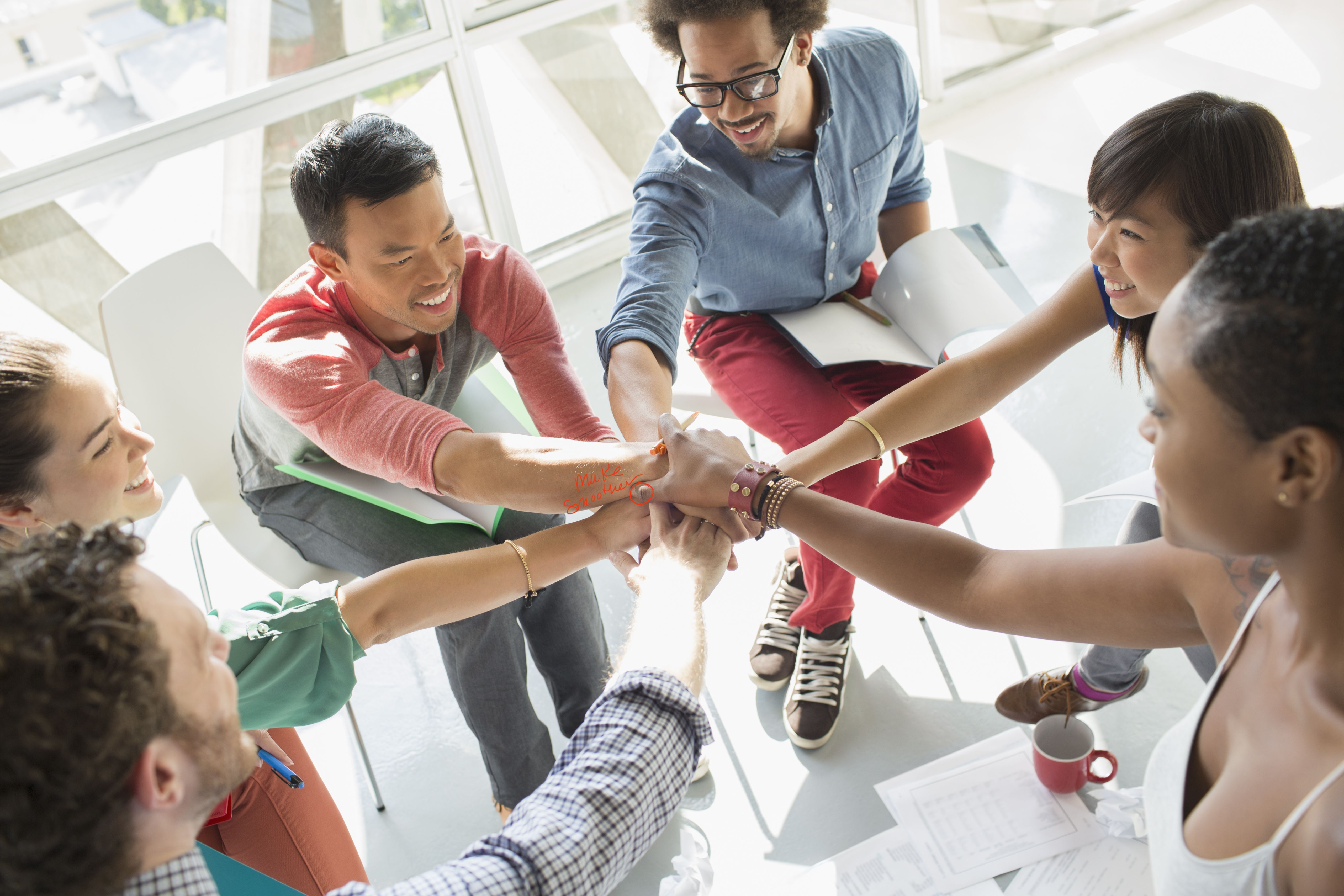 Creative business people connecting hands in huddle in a trusting work environment.