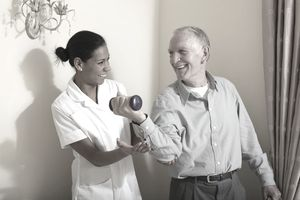 Nurse helping older man exercise at home