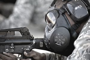 Air Force Basic Military Training trainee fires at his target while wearing his gas mask.