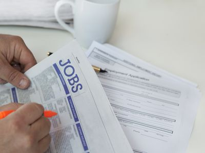 Unemployed man circling posts in the Jobs section of a newspaper
