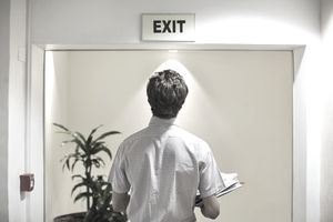 Businessman examining exit sign in office