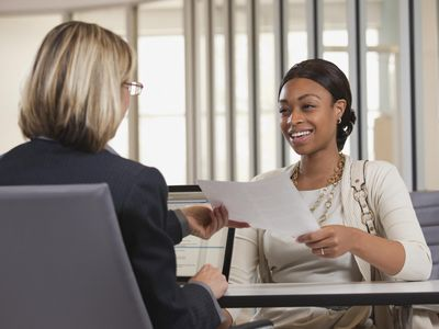 Business woman handing paper to coworker