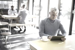 Older man using digital tablet in cafe