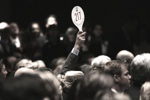 A man holds his hand up while bidding on a work of art inside the auction house Christie's