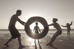 Family playing with rubber ring on beach