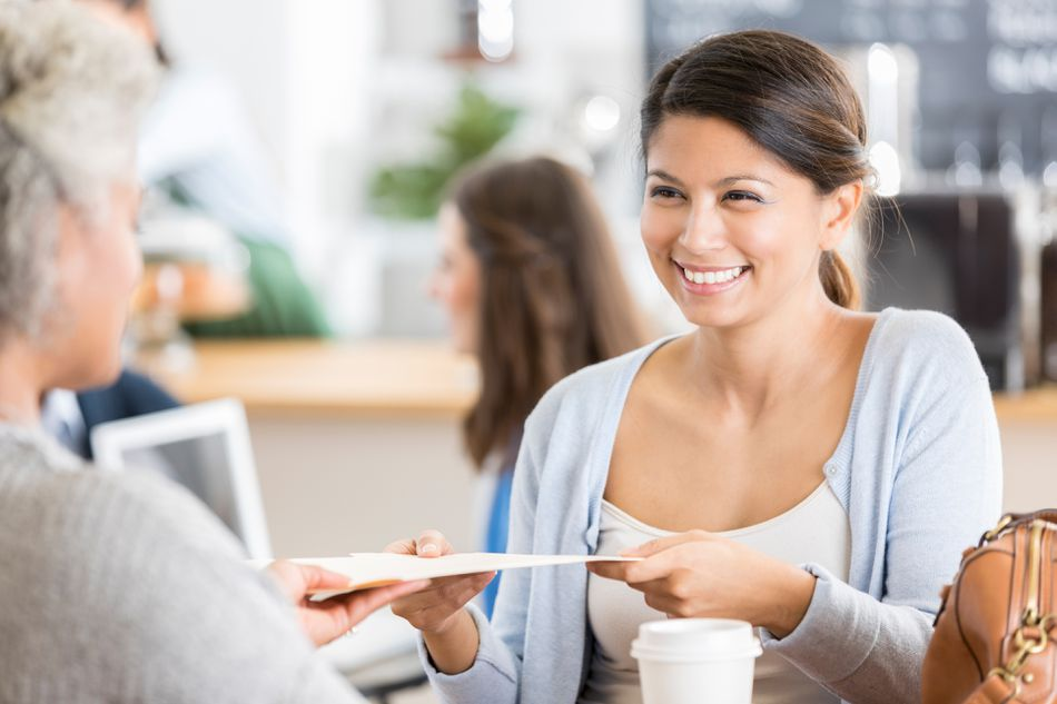 Businesswoman meets with interviewer in coffee shop