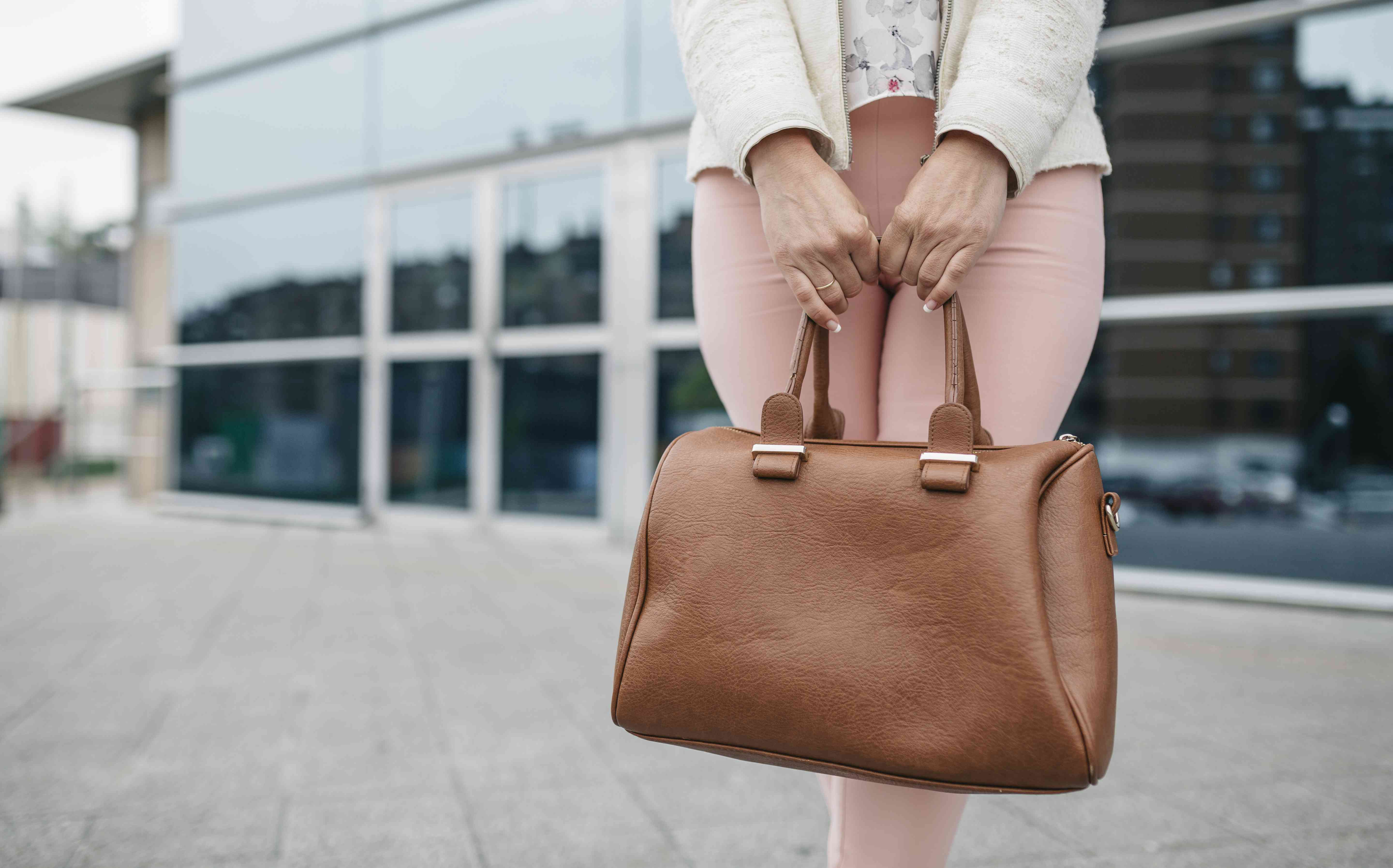 Woman holding large handbag in front of an office