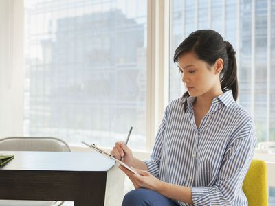 Young businesswoman writing a referral request letter in office