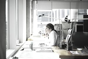 a young person sitting at desk looking out window