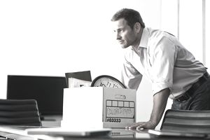 Man with box at desk
