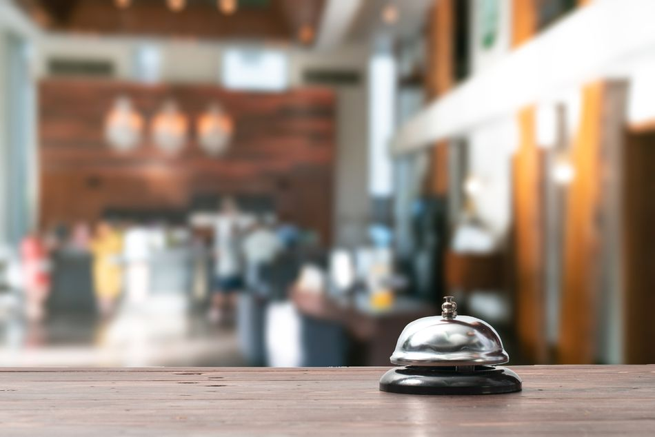 Hotel service bell on a table white glass and simulation hotel background.