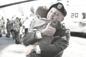 A soldier hugging his child in front of a helicopter
