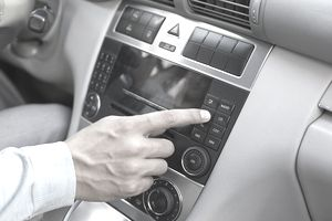 A photo of a man pressing a radio button in his car