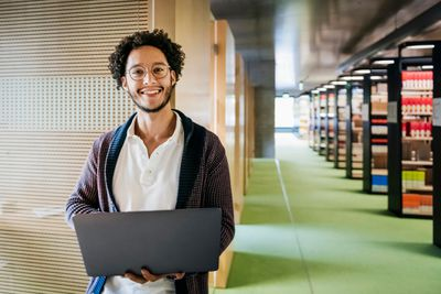 Portrait Of Young Man Holding Laptop In Library