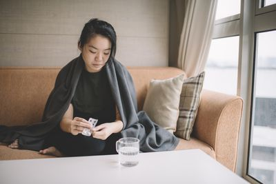 Female sitting on sofa with sickness cover with blanket taking medicine