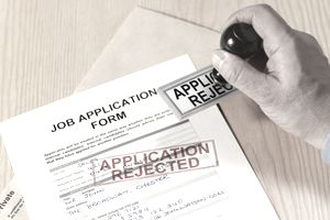 "Man stamping a job application, ""application rejected."""