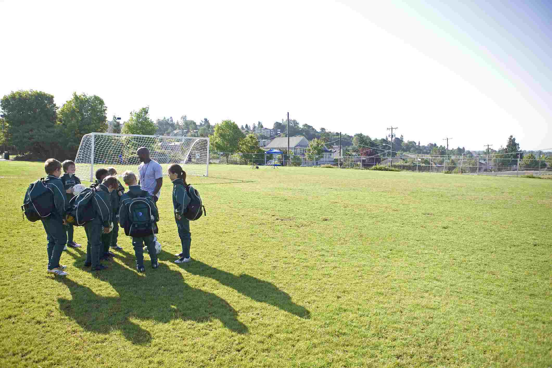 kids and coach on soccer field