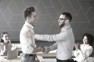 Team leader handshaking employee congratulating with professional achievement or promotion