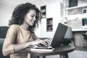 Woman typing a resume cover page on a laptop.