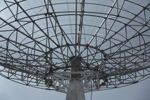 A large communication radar dish against blue