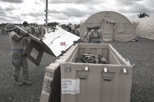 a soldier folding a box in front of a storage box in the field