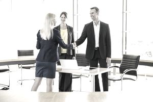 a woman with two people shaking hands in an office