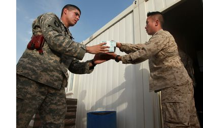 U.S. Marine Corps Cpl. David Che, right, a supply warehouse clerk with Headquarters and Service Company