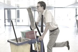 a young man pushing cleaning cart
