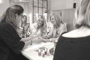 Female nail technician giving manicure to mother and adult daughters in nail salon