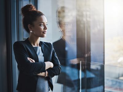 Shot of a young businesswoman looking out the window in an office
