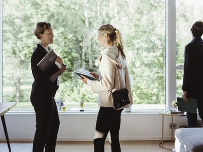 Real estate agent talking to female while standing in new house