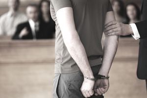 Handcuffed man standing in courtroom