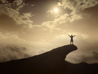 Hiker in Triumphant Pose on top of a mountain