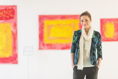 Woman curator with paintings in a museum