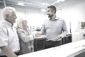 Salesman handshaking with senior couple in appliance store