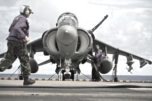 Aviation boatswain's mates refuel an AV-8B Harrier jet aircraft.