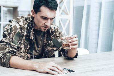 soldier in fatigues holding a drink