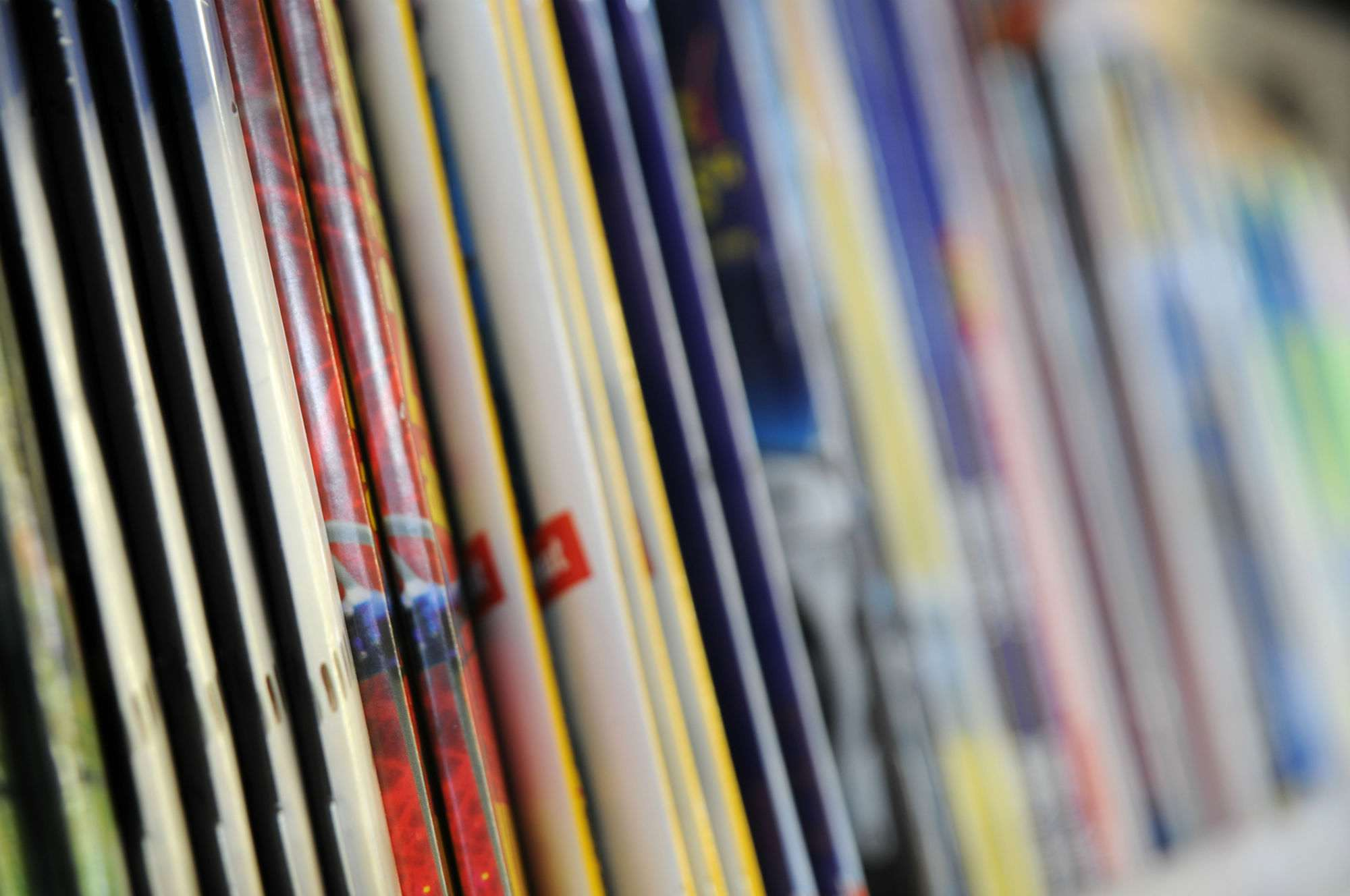 A row of thin, staple-bound magazines in a kiosk