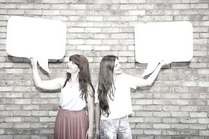 two young woman holding up and looking at speech bubbles