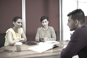 Women and man having meeting in office.
