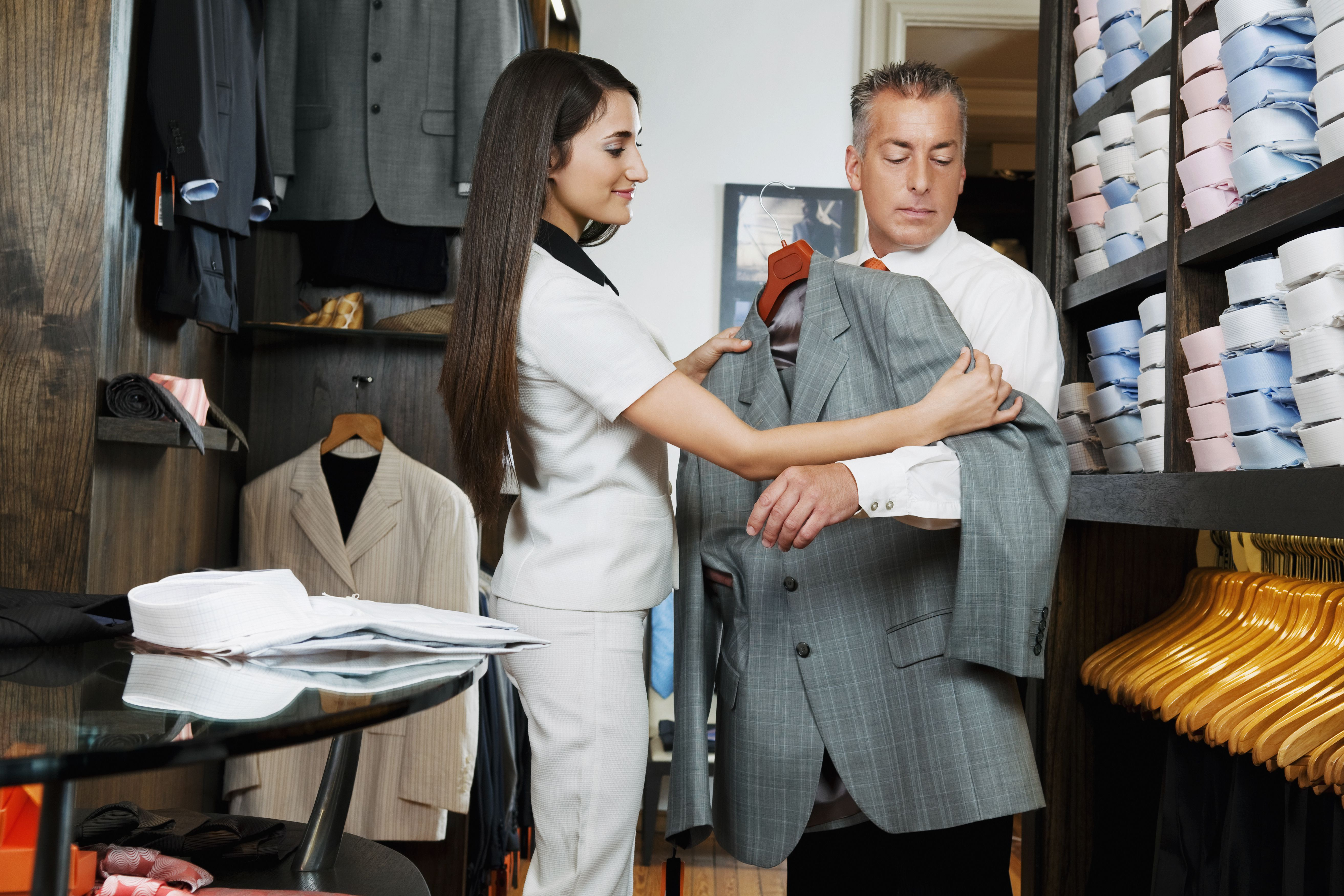 Saleswoman assisting a businessman in a clothing store