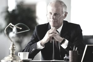 an older businessman sitting at a desk